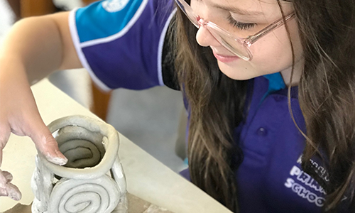 Junior potters from Millner Primary School are turning clingy clay into utilitarian containers.
