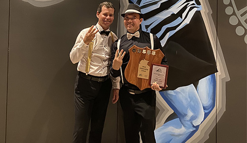 Mathew Ryan (right) gives a three-finger victory salute while holding the school badged Most Outstanding School perpetual shield, and a smaller framed version. He is accompanied by former tennis and golf great Scott Draper.